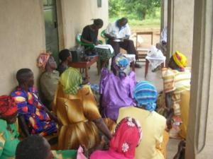 Women farmers listen to a radio show while Kubere Information Centre staff take their questions.